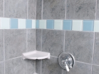 Sea green and blue glass tiles add an accent in the shower.